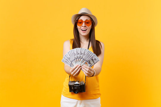 Tourist woman in summer casual clothes, hat holding bundle lots of dollars, cash money isolated on yellow orange background. Female traveling abroad to travel on weekends getaway. Air flight concept.
