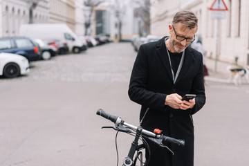 Mature man with bicycle using mobile phone