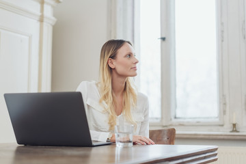 Blonde woman sitting at table with laptop