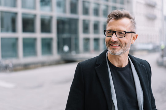 Mature smiling man with glasses wearing black coat