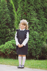 A small cheerful blue-eyed girl first-class with winded hair with bantikami and glasses in school uniform with a briefcase on September 1 is at the school in the park
