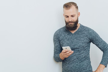 Man leaning on a white wall reading a text message