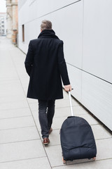 Rear view of man pulling suitcase along sidewalk
