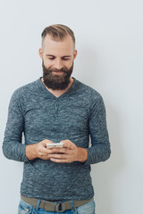 Attractive bearded man smiling at a phone message