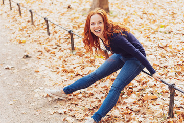 Laughing happy young woman in an autumn park