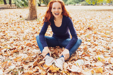 Laughing carefree young woman in a fall park