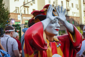 Colorful figure of a clown with arms raised.
