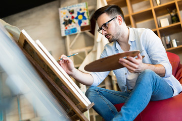 Young man painting on canvas