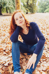 Pretty young woman relaxing in an fall park