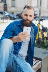 Young bearded man sitting with mobile phone