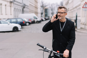 Mature man with bicycle talking on mobile phone