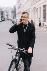 Man standing chatting on a mobile holding a bike