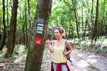 Beautiful woman smiling at path in a forest nex to a tourist sign during hiking on a hill during sunrise on summer