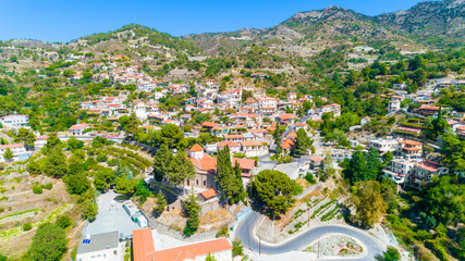 Aerial view of Agros village settlement on mountain Troodos, Limassol district, Cyprus. Bird's eye view of traditional houses with ceramic tile roof, church, countryside and rural landscape from above
