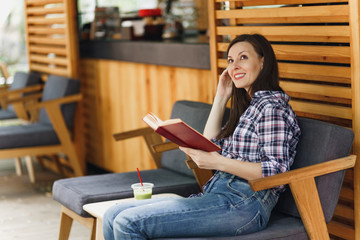Beautiful woman in outdoors street summer coffee shop wooden cafe sitting in casual clothes, reading book with cup of cocktail, relaxing in restaurant during free time. Lifestyle rest vacation concept
