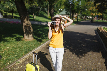 Pretty traveler tourist woman in hat with suitcase city map take pictures on retro vintage photo camera in city outdoor. Girl traveling abroad to travel on weekends getaway. Tourism journey lifestyle.