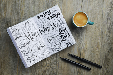 MINDFULNESS hand-lettered sketch notes in notepad on wooden desk with cup of coffee and pens