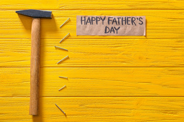 "Hammer, nails and paper with text ""Happy Father's Day"" on color wooden background"
