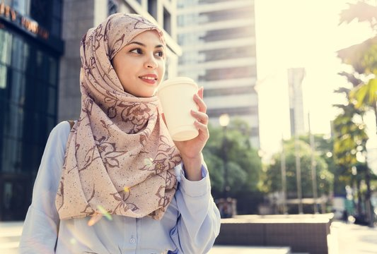 Islamic woman drinking coffee in the city