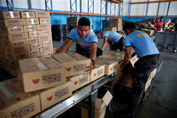 Policemen carry boxes of relief goods for victims of Super Typhoon Mangkhut at the Department of Social Welfare and Development, National Relief Operations Center in Pasay City