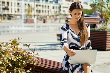 young business woman in a dress sitting on a bench and works on the computer in the summer
