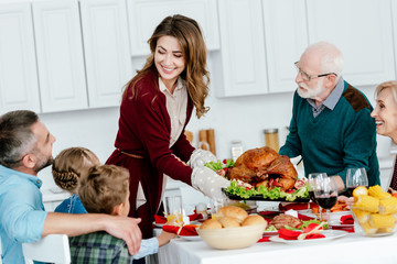 happy adult woman and senior man carrying baked turkey for thanksgiving celebration with family at home