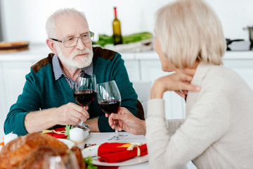 senior couple clinking by wine glasses at serve table with baked turkey on thanksgiving
