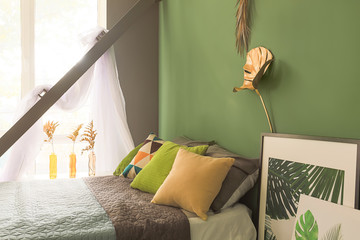 Interior of modern comfortable bedroom with golden tropical leaves on color wall