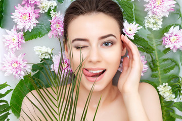 Portrait of young sexy beauty female woman with clean pure skin taking spa relaxing in bath with flowers and green leafs white soap water. Skin beauty health care concept. Body part and nature