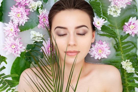 Portrait of young sexy beauty female woman with clean pure skin taking spa relaxing in bath with flowers and green leafs white soap water. Skin beauty health care concept. Body part bare shoulder