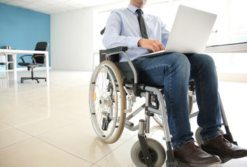 Businessman in wheelchair working with laptop in office