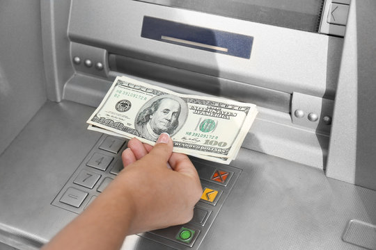 Woman withdrawing money from ATM, closeup