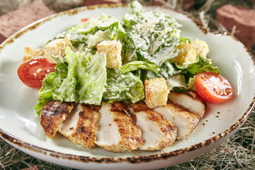 Caesar Salad with Sliced Chicken Fillet on Rustic Hay Background