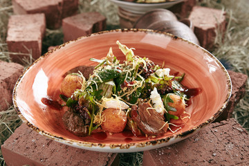 Duck Breast Salad with Crispy Potato Balls on Rustic Style Hay Background Close Up