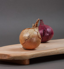 Wooden cutting board on grey background with vegetables