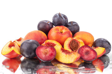 A lot of bright fruits, whole and cut peaches and plums on a mirror white background in water drops isolated
