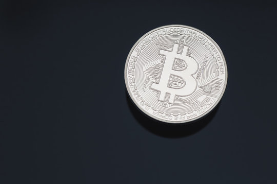Bitcoin cryptocurrency coin token close up cleaned silver macro with black background and copy space.