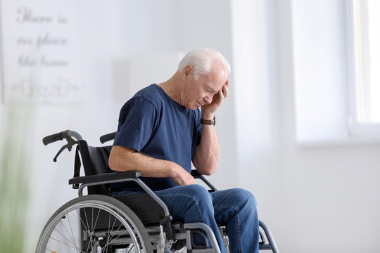 Disabled senior man in wheelchair suffering from headache at home