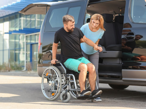 Woman helping handicapped man to sit in car