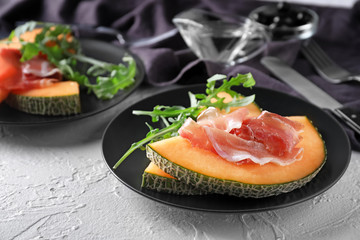 Plate with delicious melon and prosciutto on white table