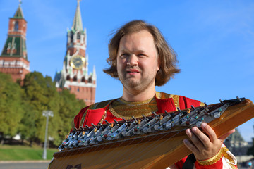 Portrait of a musician with old Russian music instrument gusli