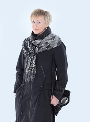 smiling woman in a black coat and scarf.isolated on white.