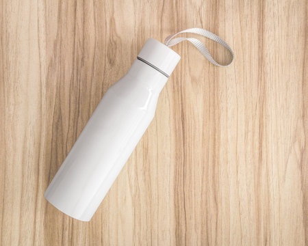White water bottle on wood background. Insulated container for keep your drink.