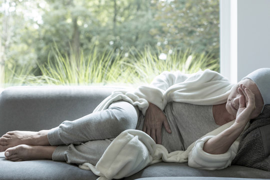 Sick woman with a headache lying on a sofa