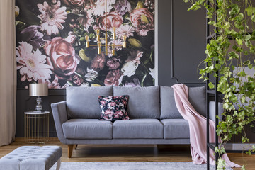 Real photo of a floral living room interior with a wallpaper, sofa and plants