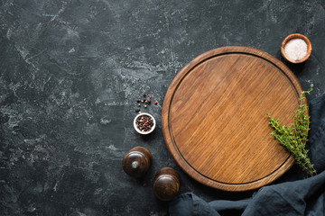 Spices, Herbs, Cutting board for cooking. Round wooden cutting board on black concrete backdrop. Top view with copy space for text. Menu, recipe mock up, banner background