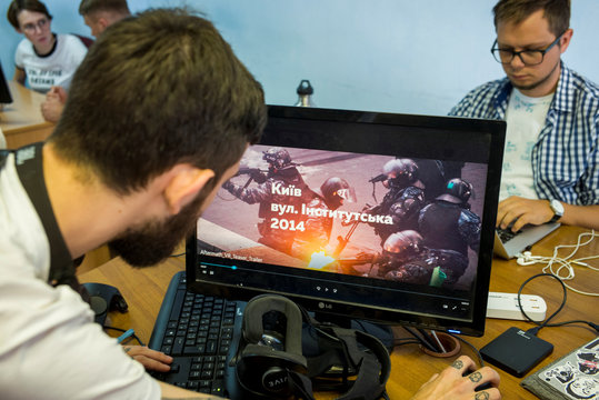 Staff members of the New Cave Media test a simulator of virtual reality in their office in Kiev