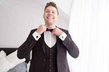 Young smiling man putting on bow tie