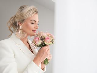 Sensual adult bride smelling bouquet
