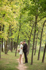 Beautiful bride and groom embracing in park